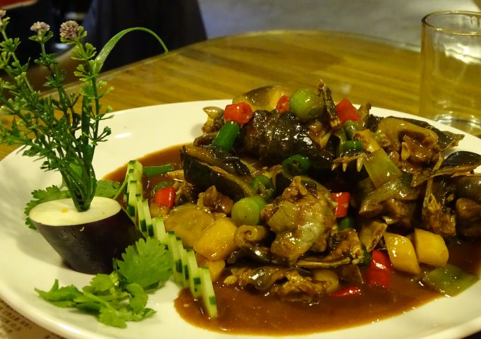 Cooked softshell turtle served on a plate with red chilies and other vegetables